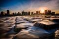 Картинка небо, вода, солнце, закат, город, камни, дома