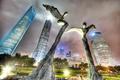 Картинка скульптура, небо, дома, вечер, огни, небоскреб